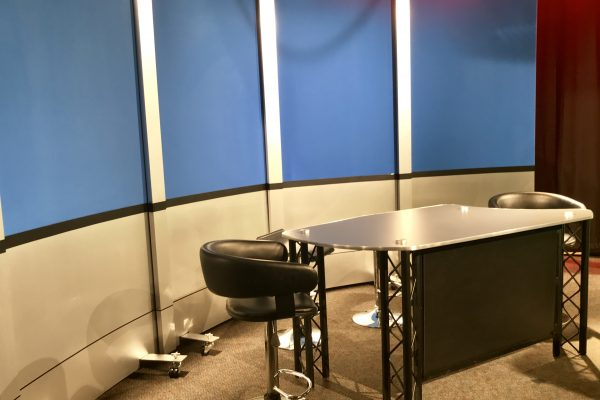 Reversible rolling panel set background solution for access Sacramento. With brushed aluminum finishes and news interview desk