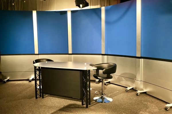 Reversible rolling panel set background solution for access Sacramento. With brushed aluminum finishes and blue veltex and news interview desk