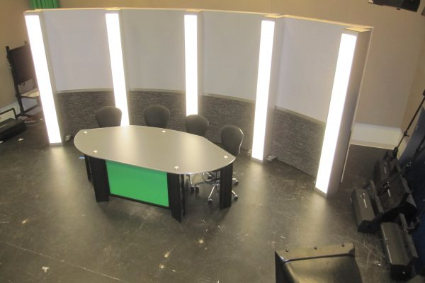 News desk for 4 - 5 talent with stone and grey set background and led light box columns