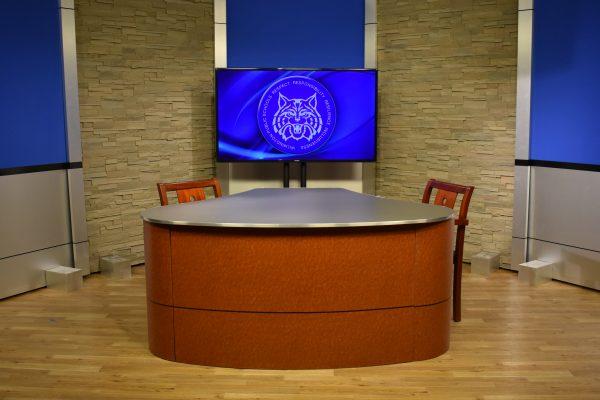 News desk, interview desk, with rolling panel set background behind. Broadcast desk finished in birds eye cognac
